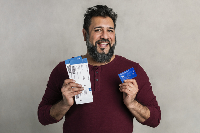 man holding a credit card and flight tickets