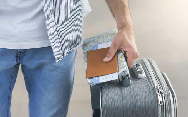 Man going to flight with suitcase, passport
